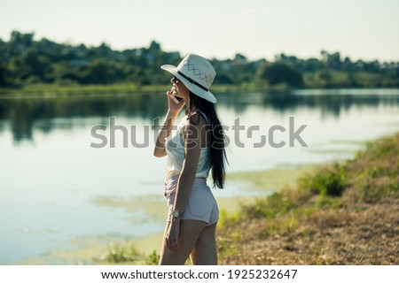Gorgeous slender brunette talking on the phone by the lake.Smiling  woman talking on the phone in mall.Sexy girl in shorts walks in the park.
