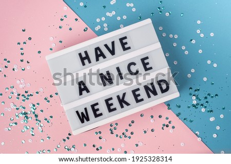 Have a nice weekend - text on display lightbox on blue and pink background.