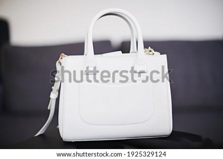 Little white handbag on grey background