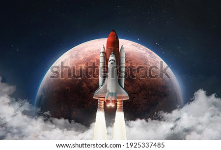 Spaceship in the outer space on orbit of Mars planet. Space shuttle in sky with clouds. Exploration of Red planet. Elements of this image furnished by NASA Royalty-Free Stock Photo #1925337485
