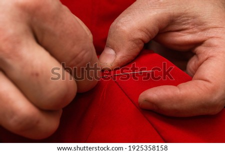 sanior old man or woman Sews with a needle and thread at home. Fingers hands of the seamstress is using a needle and red thread to sew cloth close-up Royalty-Free Stock Photo #1925358158
