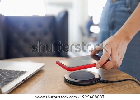 Charging mobile phone battery with wireless charging device in the table. Smartphone charging on a charging pad. Mobile phone near wireless charger Royalty-Free Stock Photo #1925408087