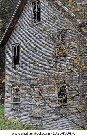 An abandoned, condemned, creepy,  clapboard home with a .  pretty pattern of  orange fall leaves in focus. The section of house is slightly blurred, with blown out windows. Royalty-Free Stock Photo #1925430470