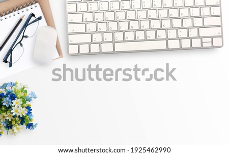 White minimal office desk table with notebook,glasses and flower and mini mouse and keyboard wireless. Top view with copy space for text or picture, flat lay.