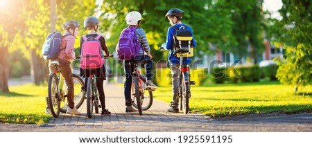 Children with rucksacks riding on bikes in the park near school. Pupils with backpacks outdoors Royalty-Free Stock Photo #1925591195
