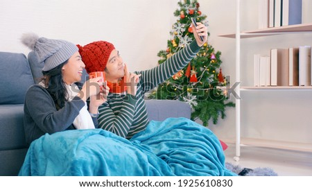 Happy Asian beautiful young family couple husband selfie and wife smile and laugh enjoying funny in living room with winter day at home. Happy holiday in winter time