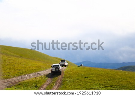 a convoy of cars is moving along a dirt road. travel by car in the mountains. rough road in the steppe. jeeps make their way through the desert Royalty-Free Stock Photo #1925611910