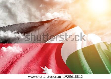 Jordan national flag cloth fabric waving on beautiful grey sky. Royalty-Free Stock Photo #1925618813
