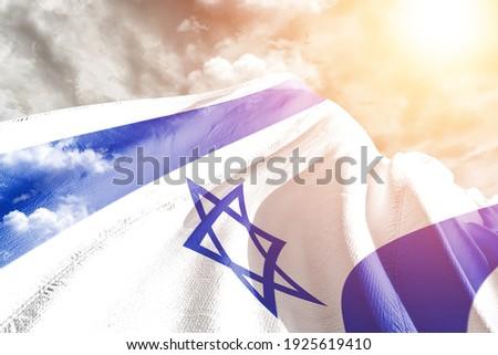 Israel national flag cloth fabric waving on beautiful grey sky. Royalty-Free Stock Photo #1925619410