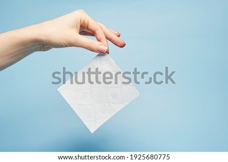 The hand that holds clean white textured toilet paper sheet with blue pattern isolated on the bright solid blue fond background
