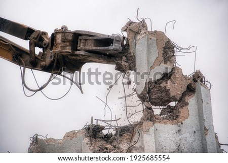 Digger demolishing building using the hydraulic arm Royalty-Free Stock Photo #1925685554