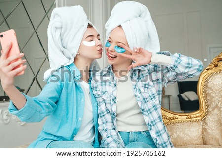 Two young beautiful smiling women with patches under their eyes.Sexy carefree models sitting on bed in posh apartment.They doing beauty treatments at home in towels on heads. Taking selfie photos