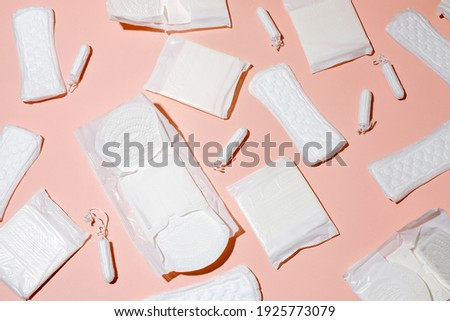 Tampons, feminine sanitary pads pattern on pink background. Hygiene care during critical days. Menstrual cycle. Caring for women's health. Monthly protection, hard shadow, copy space Royalty-Free Stock Photo #1925773079