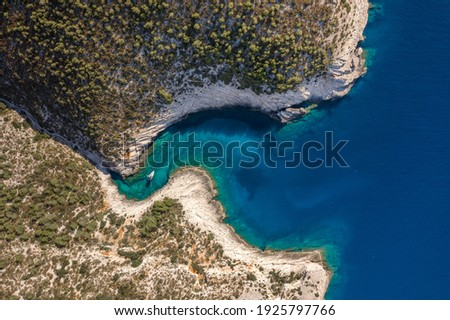 Aerial overhead drone shot of yacht on Adriatic sea curvy cove on Vis Island in Croatia summer morning Royalty-Free Stock Photo #1925797766