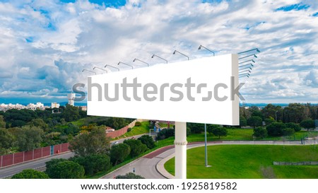 Blank billboard ready to use for mockup advertisement on the background of the city. Billboard white blank with room to add your own text. Retail, outdoor advertisement and commerce concept