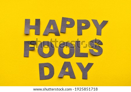 Image caption Happy Fool's Day of grey paper letters on a yellow background close-up. High quality photo