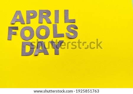 Image caption April Fools' Day of paper letters grey on a yellow background with a copy space in the style of minimalism. High quality photo
