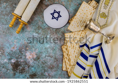 Pesach Passover celebrating symbols of great Jewish family holiday traditional matzah, kippah and tallit, torah scroll Royalty-Free Stock Photo #1925862551