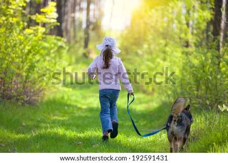 Little girl with dog running in the forest. Back to camera. #192591431