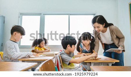 Pupil boy hi five with teacher in classroom at elementary school. Student boy studying in primary school. Children writing notes in classroom. Education knowledge, successful teamwork concept banner Royalty-Free Stock Photo #1925979224