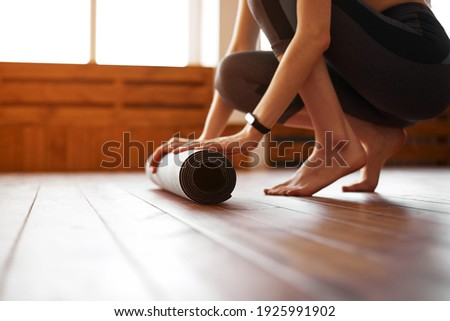 Close-up of young woman with exercise mat preparing for sports training Royalty-Free Stock Photo #1925991902