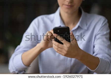 Crop close up of young Caucasian businesswoman use modern smartphone text or message with client partner online. Woman hold look at cellphone screen browse internet. Technology, communication concept. Royalty-Free Stock Photo #1926027971