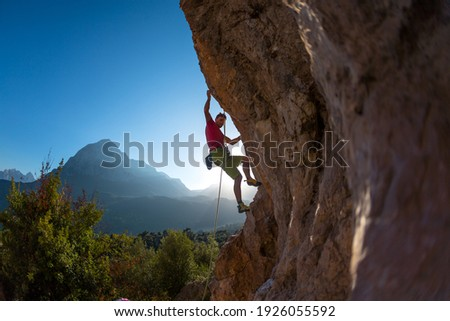 Athletic man climbs an overhanging rock with rope, lead climbing. silhouette of a rock climber on a mountain background. outdoor sports and recreation Royalty-Free Stock Photo #1926055592