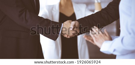 Unknown businesspeople are shaking their hands after signing a contract at meeting, close-up. Business communication concept Royalty-Free Stock Photo #1926065924