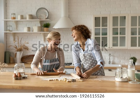 Warm relations. Happy old woman mother pensioner young female daughter grown up kid engaged in baking cookies roll dough at kitchen together laugh have fun. Elderly lady enjoy cooking with adult child Royalty-Free Stock Photo #1926115526