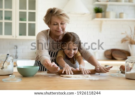 My little helper. Active aged grandma involve small grandkid girl in rolling yeast cookie dough with wooden pin. Caring elderly granny sharing skills in baking homemade pastries with little grandchild Royalty-Free Stock Photo #1926118244
