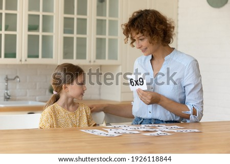 I like learning maths. Happy mother teach small child daughter mathematics using flash cards. Creative millennial female teacher help junior schoolgirl understand multiplication basics in form of game Royalty-Free Stock Photo #1926118844