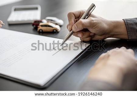 A close-up picture of the tenant who is about to sign the signature on the car rental contract with the car rental company after discussing the details with the employee. Concept of car rental.