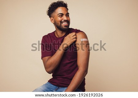 Man smiling after receiving vaccination. Man showing his arm after receiving a vaccine. Royalty-Free Stock Photo #1926192026