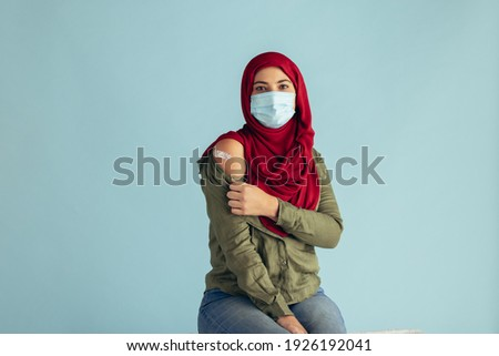 Muslim woman wearing protective face mask showing her arm with band-aid after getting vaccination. Woman in hijab received corona virus vaccine. Royalty-Free Stock Photo #1926192041