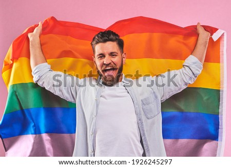 Portrait of smiling Handsome bearded young hipster gay holding an lgbtq+ flag on pink background