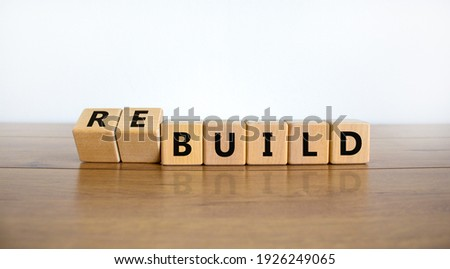 Time to rebuild symbol. Turned wooden cubes and changed the word 'build' to 'rebuild'. Beautiful wooden table, white background. Business, build or rebuild concept. Copy space. Royalty-Free Stock Photo #1926249065