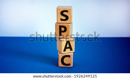 SPAC, special purpose acquisition company symbol. Wooden cubes with word 'SPAC' on beautiful white and blue background, copy space. Business and SPAC, special purpose acquisition company concept.