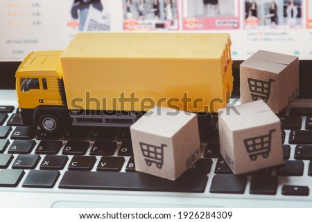 Logistics, and delivery service - Truck and paper cartons or parcel with a shopping cart logo on a laptop keyboard. Shopping service on The online web and offers home delivery.  Royalty-Free Stock Photo #1926284309