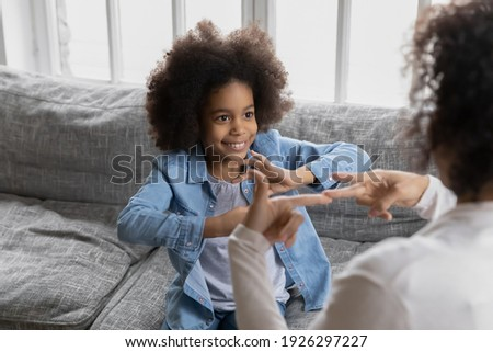 Happy girl talks to disabled deaf mom. Mother teaches kid sign language, shows hand gestures and finger symbols. Tutor giving lesson to positive child with hearing disability at home. Children therapy