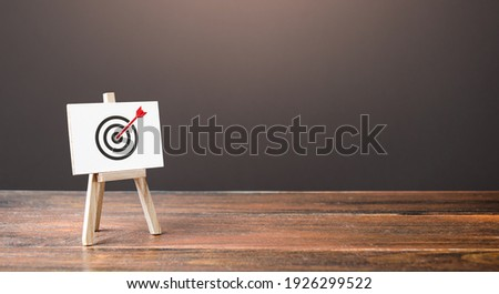 Easel with an arrow in target center. Direct hit, straight to the point. Marketing and targeting audience. Reached goal , best result. Complete success. Advertising strategy. Excellent job performance Royalty-Free Stock Photo #1926299522