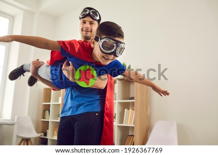 Dream big. Loving father helps his son fly like a superhero. Boy with pilot glasses play fly with his dad at home. Cheerful family in red cloaks and pilot glasses are having fun together. Royalty-Free Stock Photo #1926367769
