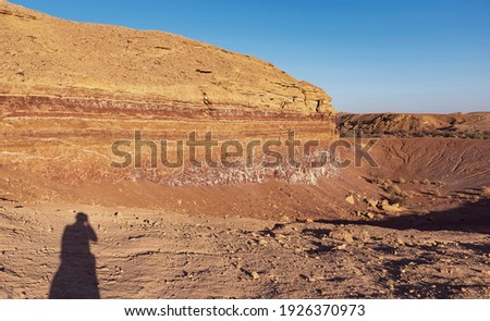 golden hour view of one of the old quarries in the makhtesh ramon crater in israel featuring the shadow of the photographer Royalty-Free Stock Photo #1926370973