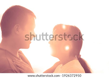 Close-up of a young couple kissing. romantic couple at sunset on bright yellow sky background, love tenderness concept, young adult peopleю sunny evening on the beach.