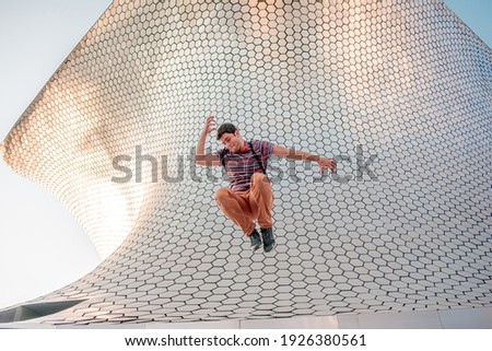 Person jumping in front of the modern and architectural Soumaya building located in Mexico City in artistic concept.