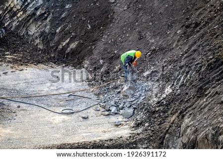 Construction worker breaking concrete reinforced  pillar at construction site.