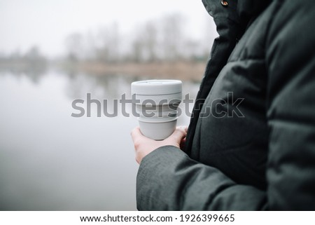 Woman holding a silicone collapsible cup, reusable coffee tumbler. Royalty-Free Stock Photo #1926399665