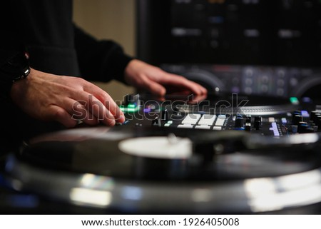 Hip hop dj scratches vinyl records with music on party in night club.Download royalty free curated images collection with dj music for design template.Royalty-free musical templates