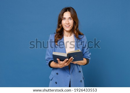 Smiling cheerful charming beautiful attractive young brunette woman 20s wearing basic jacket hold in hands reading book looking camera isolated on bright blue colour wall background studio portrait Royalty-Free Stock Photo #1926433553