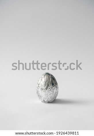 2021 Easter unique and real still life composition. Egg in aluminum foil. Space travel and food concept background.