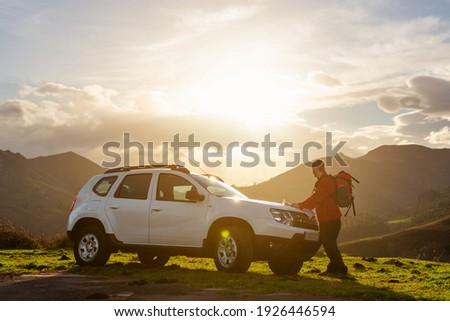 Hiker with backpack looking at a map on the hood of his off-road car at sunset. Traveler and adventurous person traces his mountain route on a map. suv vehicle. Royalty-Free Stock Photo #1926446594